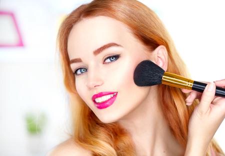 Piękna kobieta stosowania makijażu. Piękna dziewczyna patrząc w lustro i stosowania kosmetyczne z dużym pędzlem