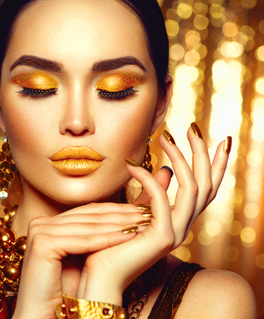 yellow: Golden holiday makeup. Fashion art manicure and makeup
