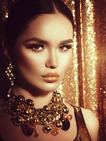 occupation: Golden holiday makeup. Golden earrings and necklace. Fashion art hairstyle, manicure and makeup