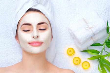 Mujer del balneario que aplica la máscara facial. Retrato de detalle de la bella joven con una toalla en la cabeza que aplica la máscara facial de la arcilla