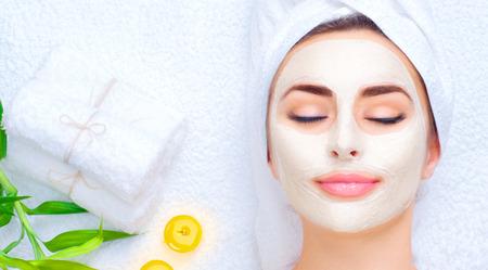 Spa Frau Gesichtsmaske. Nahaufnahmeportrait der schönen Mädchen mit einem Handtuch auf dem Kopf Gesichts-Ton-Maske der Anwendung Standard-Bild - 77096061