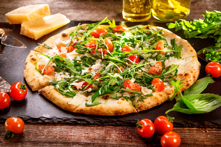 europe: Pizza Caprese with arugula, cheese, yoghurt and cherry tomatoes closeup Stock Photo