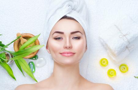 Spa, femme, application, masque facial. Close-up portrait d'une belle fille avec une serviette sur la tête appliquant masque d'argile faciale