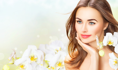 Belleza mujer con flores de orquídeas. Hermosa chica spa tocar su rostro