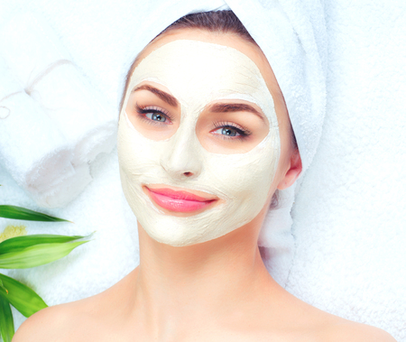 Spa woman applying facial mask. Closeup portrait of beautiful girl with a towel on her head applying facial clay mask photo