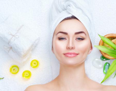 Spa Frau Gesichtsmaske. Nahaufnahmeportrait der schönen Mädchen mit einem Handtuch auf dem Kopf Gesichts-Ton-Maske der Anwendung Standard-Bild - 77096079