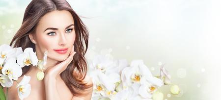 Schoonheid vrouw met bloemen orchidee. Prachtige spa meisje wat betreft haar gezicht Stockfoto