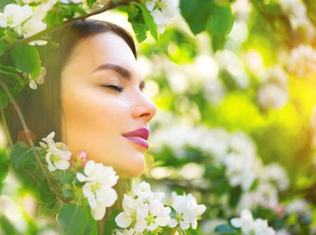 Mooie jonge vrouw die lente natuur geniet in bloeiende appelboom en glimlachen