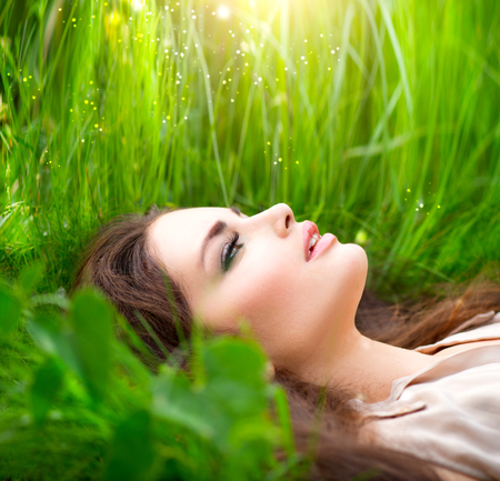dream land: Beauty woman lying on the field in green grass. Enjoying nature