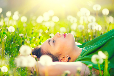 Beautiful young woman lying on the field in green grass and dandelions 스톡 콘텐츠