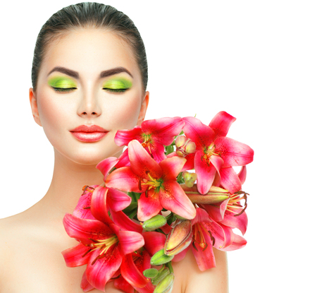 Beauty girl with lilly flowers bouquet. Beautiful spa model with blooming pink lily flowers