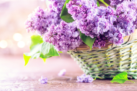 Lilac flowers bunch in a basket over blurred wood background Imagens