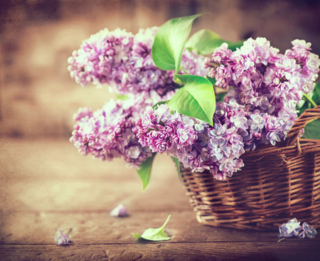 design: Lilac flowers bunch in a basket over blurred wood background Stock Photo