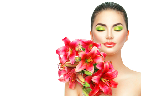 fashion: Beauty girl with lilly flowers bouquet. Beautiful spa model with blooming pink lily flowers