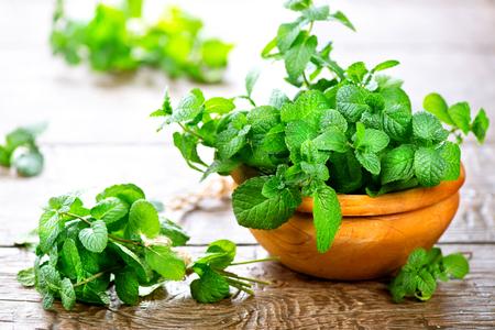 Munt. Bos van vers groen organisch muntblad op houten tafel close-up Stockfoto
