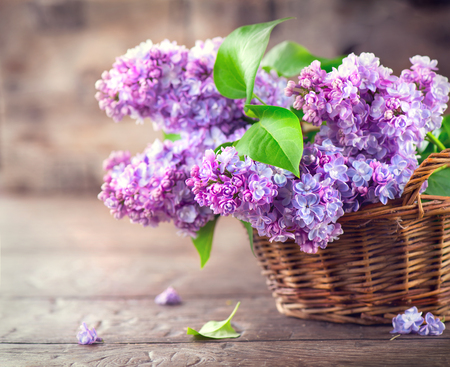 Lilac flowers bunch in a basket over blurred wood background Standard-Bild