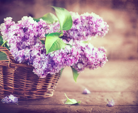 composition: Lilac flowers bunch in a basket over blurred wood background Stock Photo