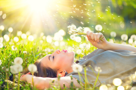 Beautiful young woman lying on the field in green grass and blowing dandelion Zdjęcie Seryjne - 78264157