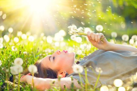 Hermosa mujer joven acostado en el campo de hierba verde y soplando diente de león