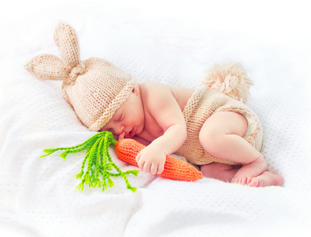 Cute two weeks old smiling newborn baby boy wearing knitted bunny costume, hat with rabbit ears, tail and funny carrot toy. Sweet baby portrait Stock Photo