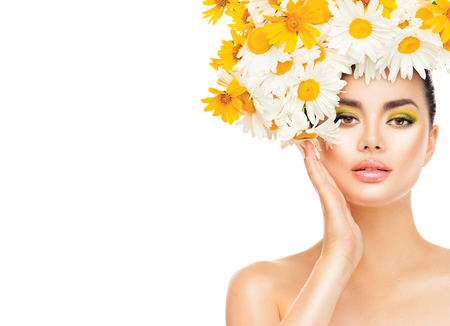 face to face: Beauty girl with daisy flowers hairstyle touching her skin. Model woman with blooming chamomile flowers