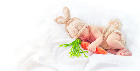 white: Cute two weeks old smiling newborn baby boy wearing knitted bunny costume, hat with rabbit ears, tail and funny carrot toy. Sweet baby portrait Stock Photo