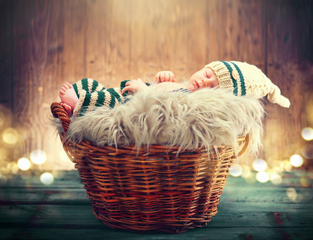 Two weeks old infant baby wearing knitted funny costume, sleeping in a basket over wooden background. Sweet newborn baby portrait Imagens - 78822951