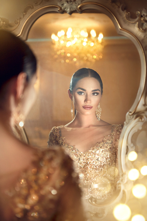 Beauty glamour lady looking in the mirror. Gorgeous woman in beautiful evening dress in luxurious style room