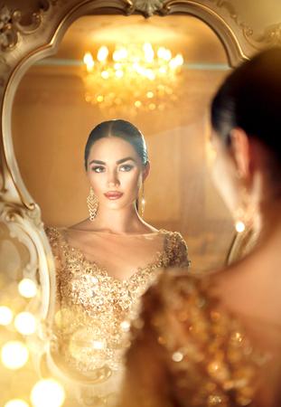 Beauty glamour lady in de spiegel kijken. Prachtige vrouw in mooie avondjurk in luxe stijl kamer
