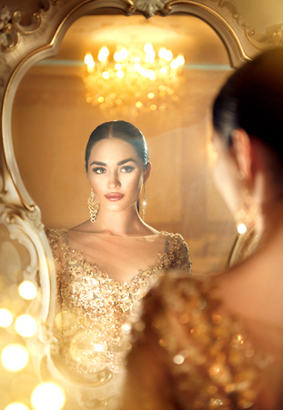 contemporary: Beauty glamour lady looking in the mirror. Gorgeous woman in beautiful evening dress in luxurious style room