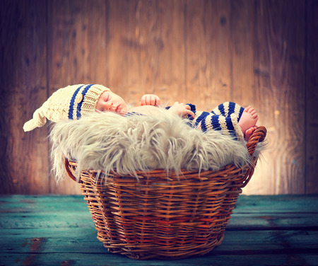 Two weeks old infant baby wearing knitted funny costume, sleeping in a basket over wooden background. Sweet newborn baby portrait