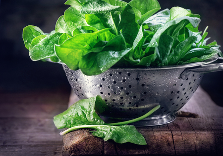 Spinach. Fresh organic spinach leaves in metal colander on a wooden table. Vegan food, healthy eating Stock Photo