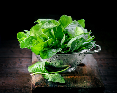 Spinach. Fresh organic spinach leaves in metal colander on a wooden table. Vegan food, healthy eating Standard-Bild
