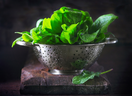 heap: Spinach. Fresh organic spinach leaves in metal colander on a wooden table. Vegan food, healthy eating Stock Photo