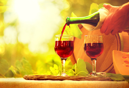 europe: Red wine and cheese. Romantic lunch outdoor. Pouring wine close-up