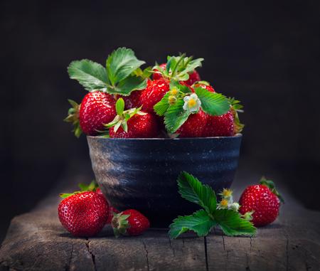 Aardbeien in een kom met blad en bloeiende bloem close-up over houten achtergrond