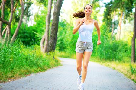 Beauté jeune femme avec des écouteurs qui courent dans le parc. Portrait complet Banque d'images - 79663447
