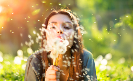 white: Beautiful young woman lying down on the field in green grass, blowing dandelions and smiling