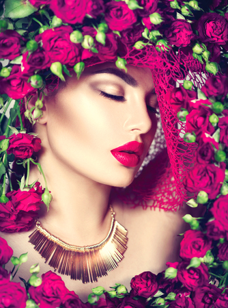 fashion: Beauty model girl with pink roses flower wreath and fashion make up. Flowers hairstyle Stock Photo