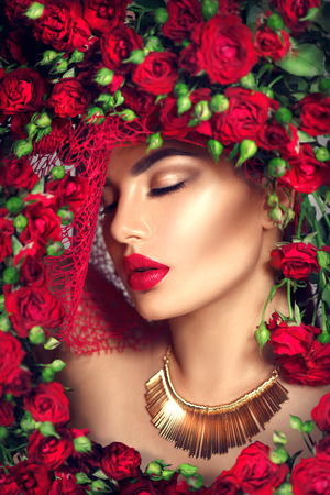 Beauty model girl with red roses flower wreath and fashion make up. Flowers hairstyle Stock fotó