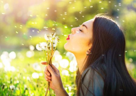 タンポポを吹くと、笑顔の美しい若い女性 写真素材
