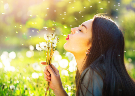 Beautiful young woman blowing dandelions and smiling Фото со стока