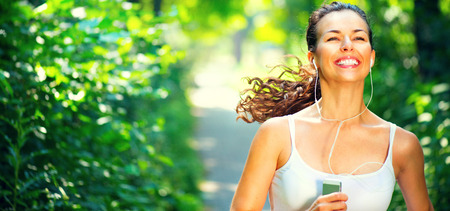 Running sporty girl. Beauty young woman with earphones jogging in the park photo