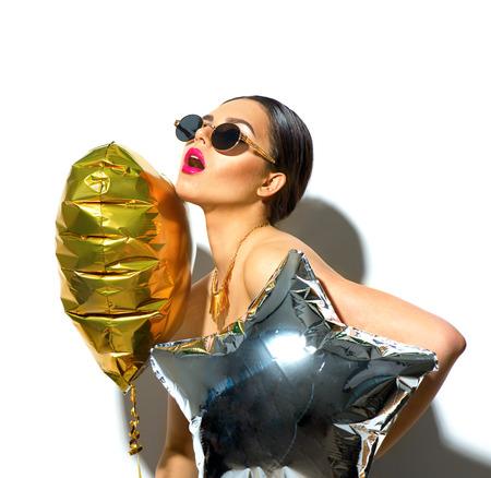 Feest. Mooi mode model meisje met kleurrijke hart en stervormige ballonnen geïsoleerd op een witte achtergrond