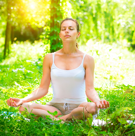 Yoga. Young woman doing yoga exercises outdoors. Meditation photo