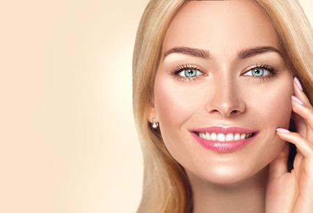 Mujer de spa de belleza tocando su rostro y sonriendo. Concepto de cuidado de la piel Foto de archivo - 80688521