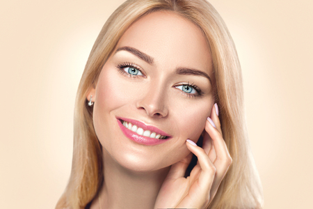 Beauty spa woman touching her face and smiling. Skincare concept Standard-Bild