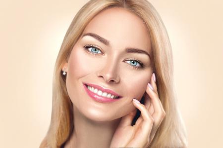 Mujer de belleza spa tocando su rostro y sonriendo. Concepto de cuidado de la piel