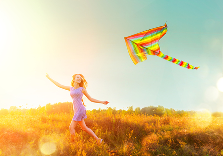 Beauty girl in short dress running with flying colorful kite over clear blue sky. Freedom concept