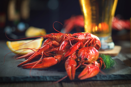 plate: Red boiled crayfish with lemon and herbs on stone slate. Crawfish closeup Stock Photo
